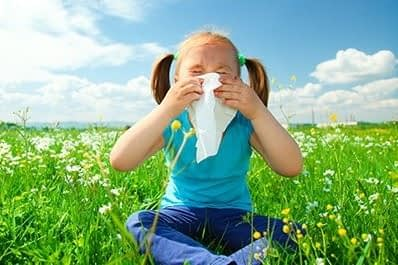 mała dziewczyna dmuchająca nos w chusteczkę