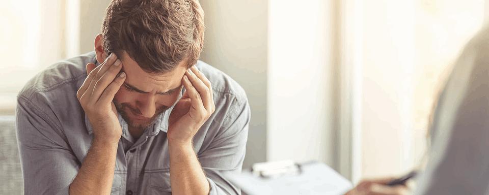 Mężczyzna trzymający się za głowę - wizyta u psychiatry